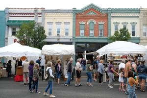 <p>Visitors look over art work along Main Street in Bowling Green during the annual Black Swamp Arts Festival Saturday afternoon.</p>