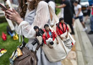 <p>Yasuyo, from Yokahama, Japan, carries her Michael Jackson dolls as she pays her respects at Jackson's mausoleum at Forest Lawn Cemetery In Glendale, Calif., on the 10th Anniversary of Jackson's death on Tuesday, June 25, 2019. Fans are gathering to pay tribute to the King of Pop, with fans congregating his former home, the cemetery where he is interred and his star on the Hollywood Walk of Fame. His estate is calling on the superstar's fans to perform acts of service in Jackson's memory. (AP Photo/Richard Vogel)</p>