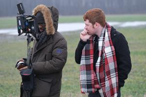 <p>Writer and director Tyler Savino (right) looks over a monitor with first camera assistant Brandon Peck along Solether Road, just east of Portage, Tuesday morning.</p>