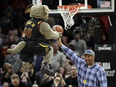 9d5bb80c8 Former Cavaliers  standout Larry Nance Sr. holds the ball for team mascot  Moondog during a timeout in the first half of Thursday s game against the  ...
