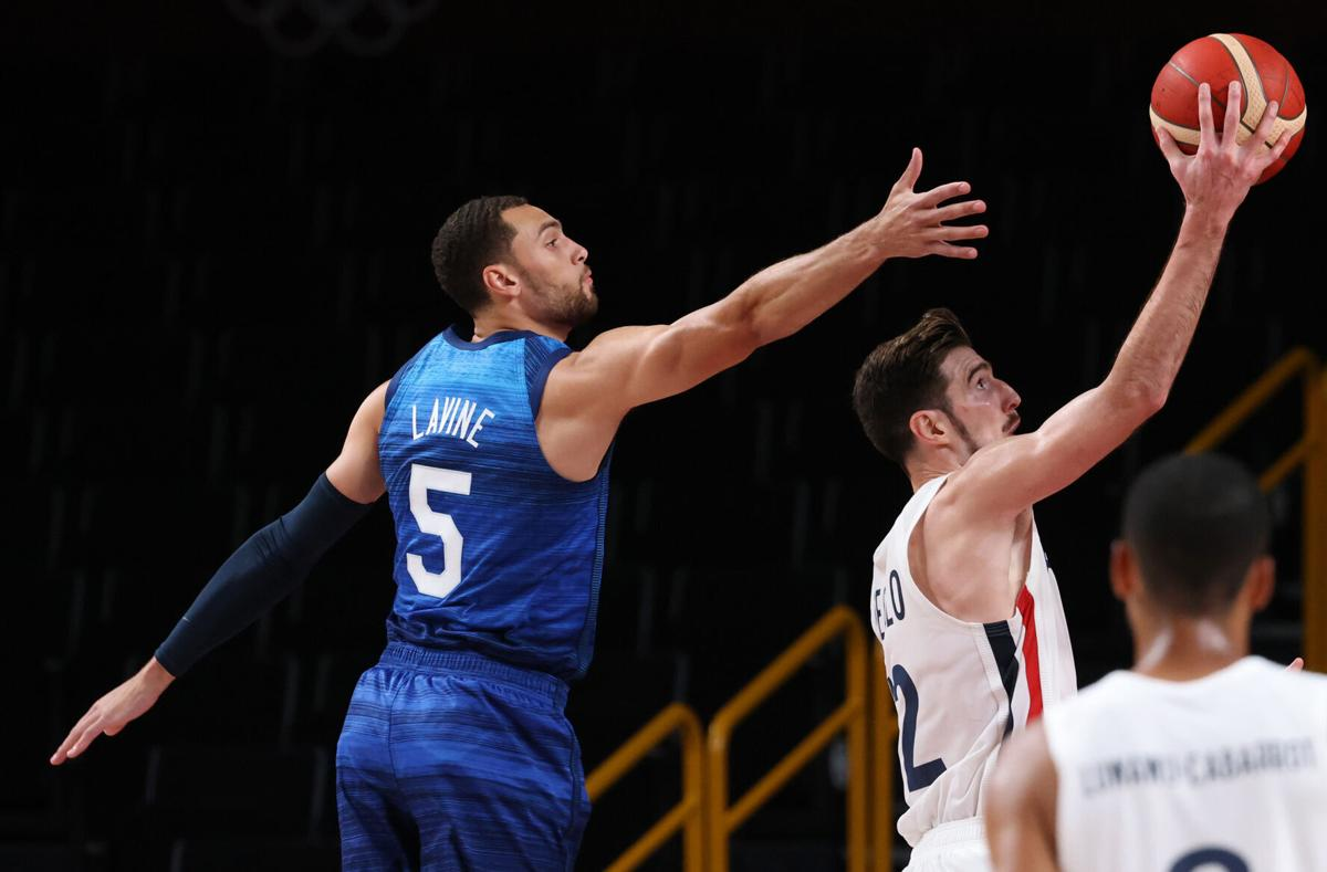 Team France shooting guard Nando de Colo slips by Team United States guard Zachary Lavine for a basket in the first half on Sunday, July 25, 2021 at Saitama Super Arena in Tokyo, Japan.