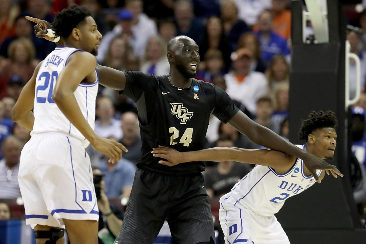 Cam Reddish (2) and Marques Bolden (20) of the Duke Blue Devils defend Tacko Fall (24) of the UCF Knights during the first half in the second round game of the 2019 NCAA Men's Basketball Tournament at Colonial Life Arena on March 24, 2019 in Columbia, S.C. (Streeter Lecka/Getty Images/TNS)  **FOR USE WITH THIS STORY ONLY**