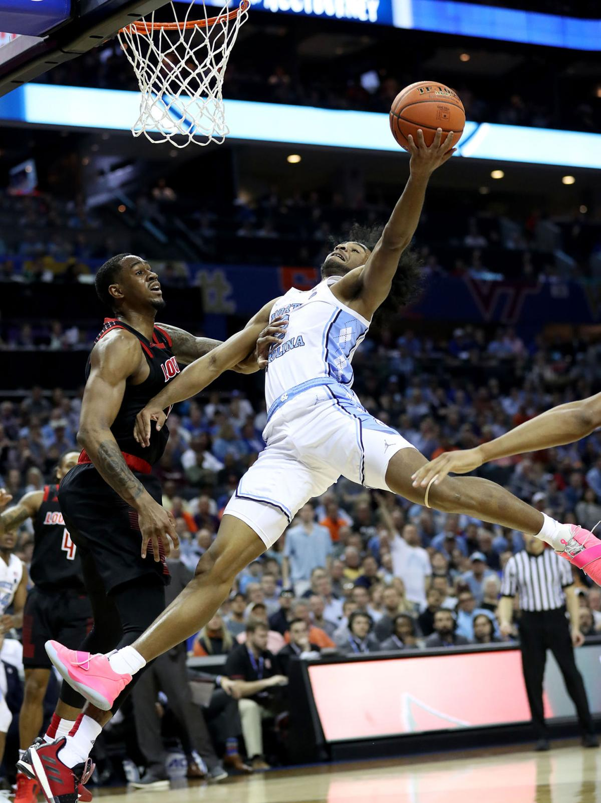 North Carolina's Coby White (2) drives to the basket against Louisville's V.J. King during the quarterfinal round of the ACC Tournament at Spectrum Center in Charlotte, N.C., on Thursday, March 14, 2019. The Tar Heels advanced, 83-70. **FOR USE WITH THIS STORY ONLY**
