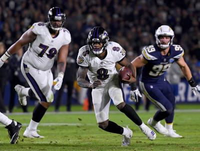The Baltimore Ravens' Lamar Jackson (8) scrambles, with blocking help from Orlando Brown, left, against the Los Angeles Chargers at StubHub Center in Carson, Calif., on December 22, 2018. (Harry How/Getty Images/TNS) **FOR USE WITH THIS STORY ONLY**