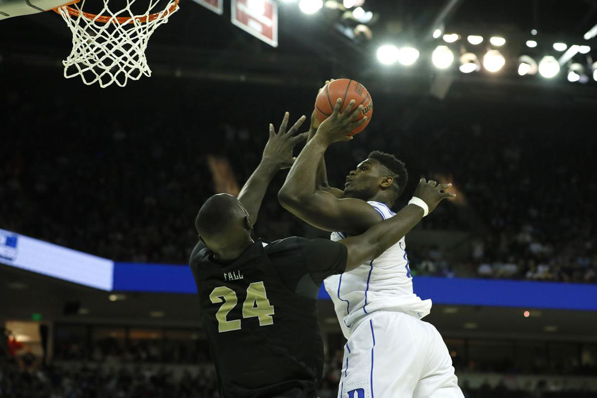 Zion Williamson (1) of the Duke Blue Devils shoots the ball as he gets fouled by Tacko Fall (24) of the UCF Knights during the second half in the second round game of the 2019 NCAA Men's Basketball Tournament on Sunday, March 24, 2019 at Colonial Life Arena in Columbia, S.C. (Kevin C.  Cox/Getty Images/TNS)  **FOR USE WITH THIS STORY ONLY**