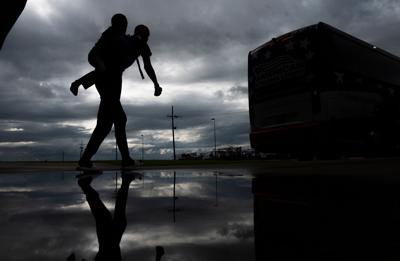 A man carries a child on his back as he walks to board a bus for evacuation before the arrival of hurricane Laura in Lake Charles, Louisiana on August 25, 2020 amid the coronavirus pandemic.