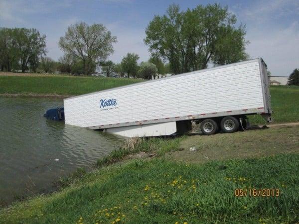 Semi-tractor trailer rolls into a pond