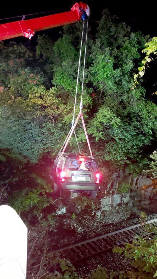 Man goes down embankment near bridge, lands on railroad tracks