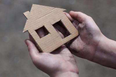 homeless hands with house