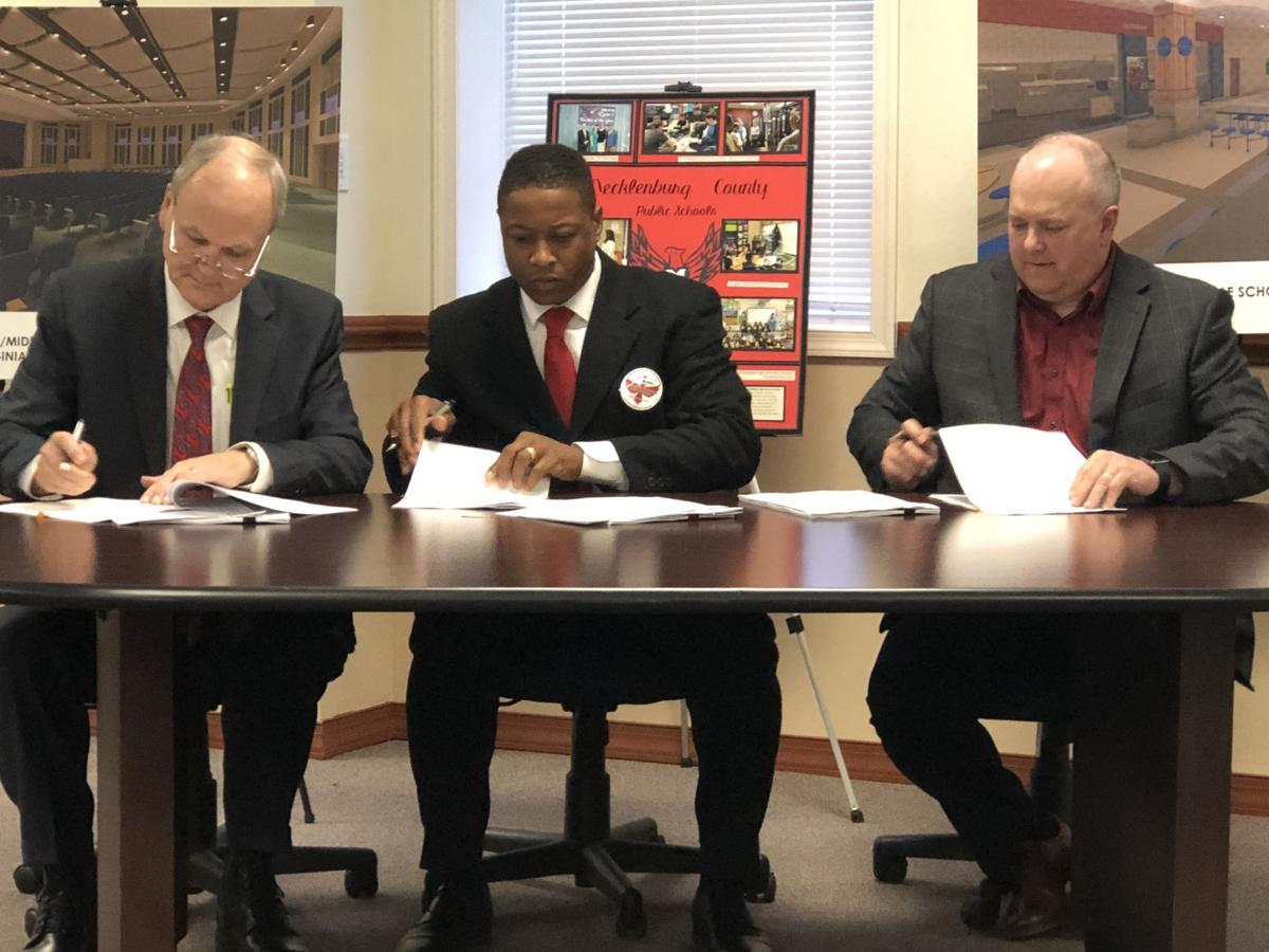 Mecklenburg County School Superintendent, Paul Nichols, School Board Chairman, Dale Sturdifen, and Cleveland Construction Vice President, Keith Zeigler sign contracts for the new school construction.
