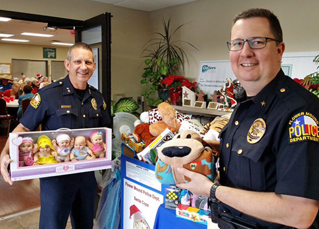 Flower Mound Police Chief Andy Kancel, left, and Assistant Police Chief Wendell Mitchell help sort out toys for Santa Cops during a previous year.