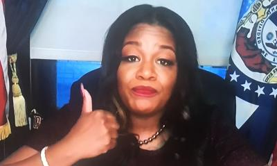 Cori Bush gestures for Trump to get out