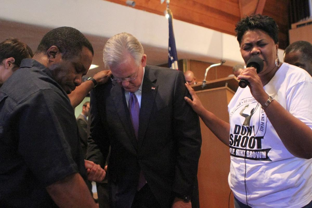 Rev. Traci Blackmon prays with Gov. Jay Nixon