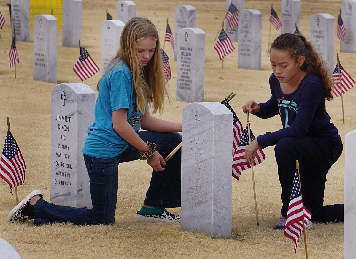 Flower Mound Public Schools students place flags at Fort Sill National Cemetery in Elgin