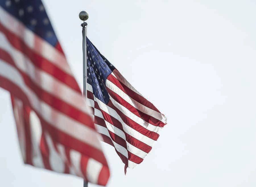 LaFontaine Used Cars of Fenton on Silver Parkway is adorned with several American flags on light, and flag poles.