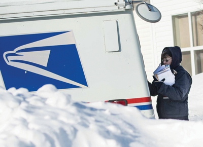 Letter carrier Sue Rearson delivers mail on Jan. 6. A letter currently costs 46 cents to ship.