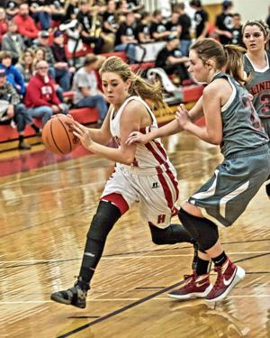 Holly's Rebecca Fugate (left) dribbles the ball in a game last winter. Fugate has scored at least 20 points in each of Holly's contests this season, helping the Bronchos to a 2-0 start.