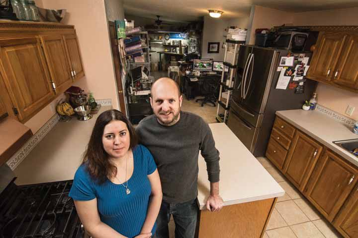 Jennifer and Patrick DeGuise stand in the spacious kitchen in their nearly 2,000-square-foot home in Fenton Oaks Manufactured Home Community in Fenton. The home is large enough for a 260-square-foot work area, shown here toward the back of their home.