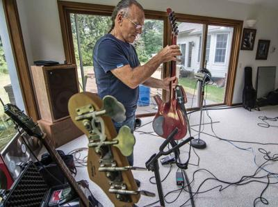 """Mark Farner picks up his Parker guitar before a recording session in Tyrone Township Monday. The rock 'n roll legend of Grand Funk Railroad fame has ties to Flint and Parshallville, where he recorded some famous rock classics. Now he has ties to Fenton, recording the new single, """"The Prisoner."""""""