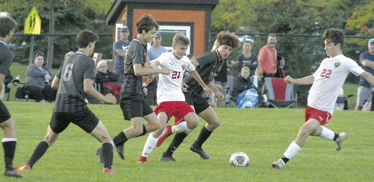 Linden's Alex Smith (21) and Aiden Miller (22) battle withFenton's Max Guerra (middle) and Vincil Harrison (far left) for a ball in the Eagles' 2-0 victory.