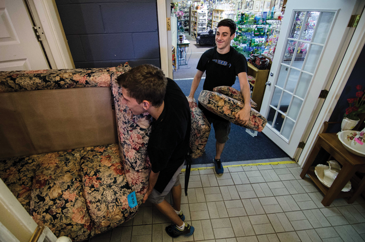 David Burgess, 16, helps move a sold loveseat into an employee area, as Keenan Hasenfratz, 16, carries seat cushions.