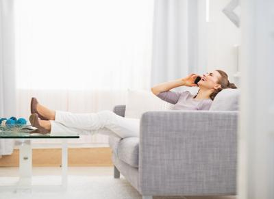 Happy young woman talking cell phone while sitting on sofa