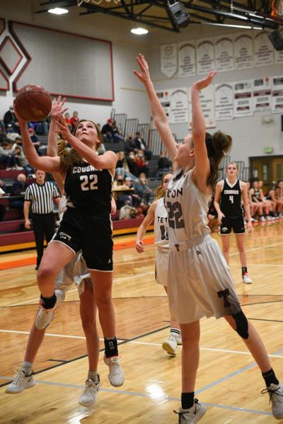 South Fremont's Rylie Neville lays on up between Teton defenders in the Cougars' 47-44 win over the Timberwolves in Driggs.