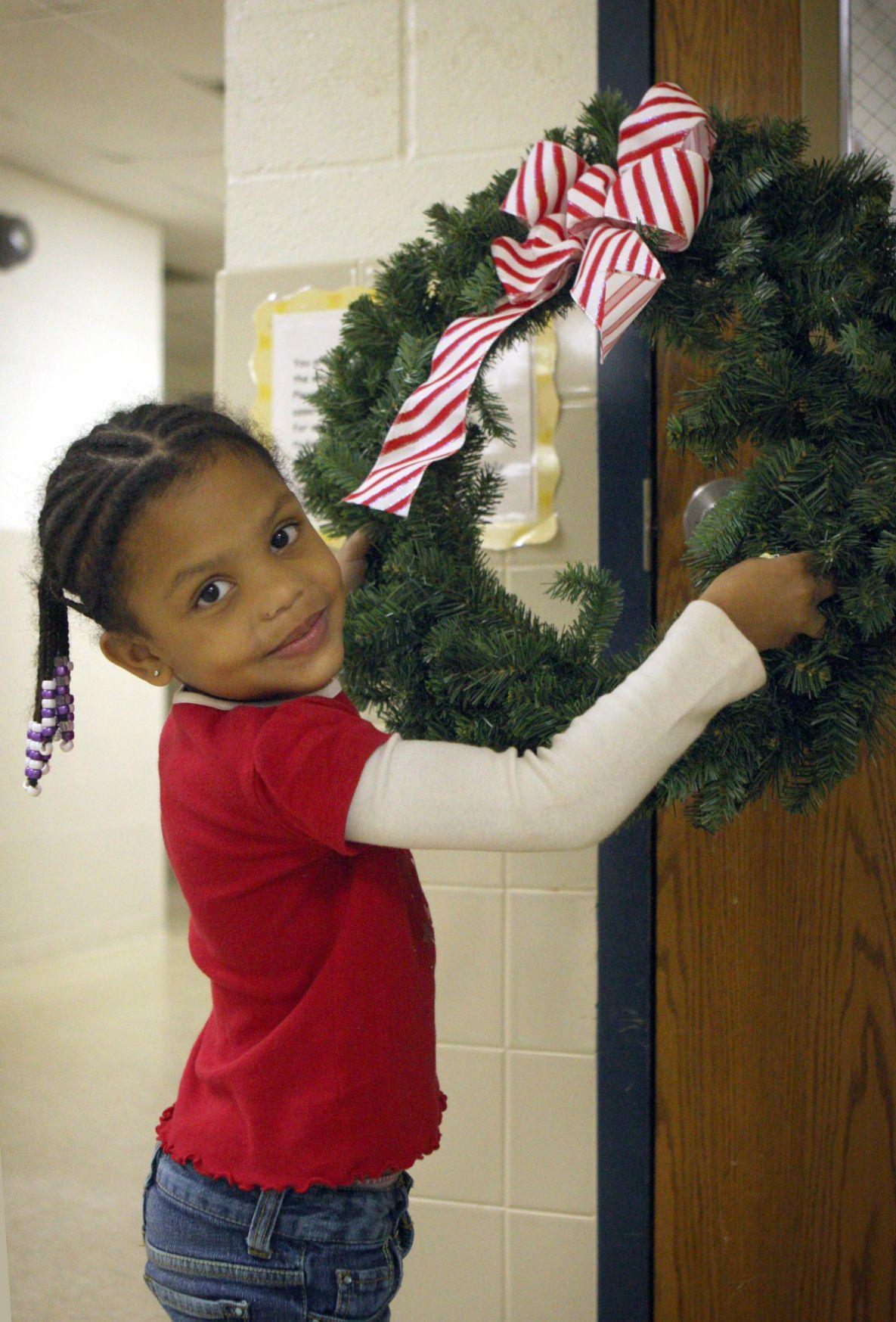 Pre-K student Justice Warrior hangs a Christmas wreath on her classroom door..jpg