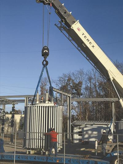 An employee helps guide the 20,000 pound transformer