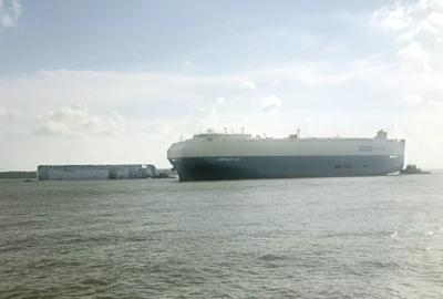 Carrier ship passes tipped freighter, departing from the port
