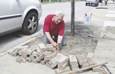 Mike Largarticha works on improving the appearance of Main Street by working on several tree beds.