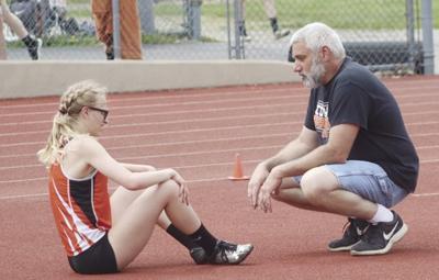 Coach Todd Knapp talks with high jumper Mackenzie Campbell.