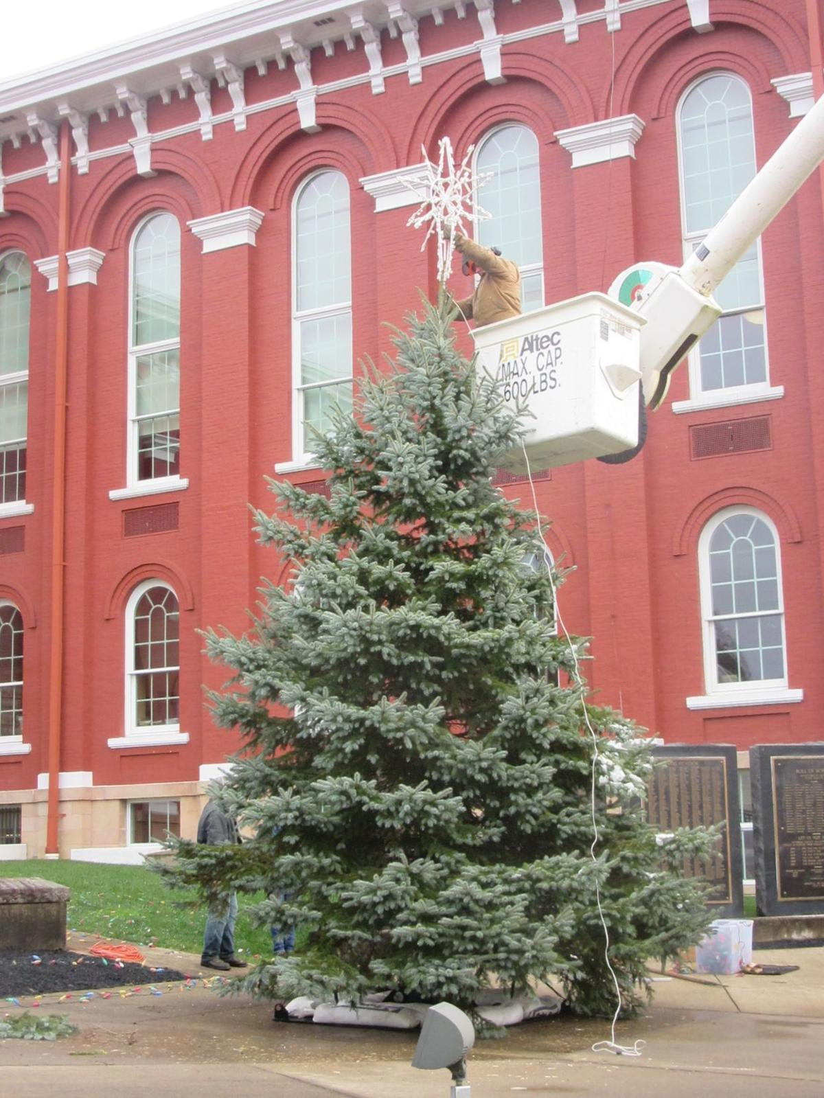 Placing the star on the community Christmas tree