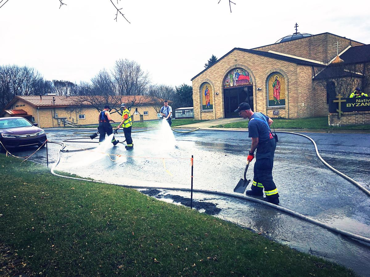 Firefighters wash down church parking lot