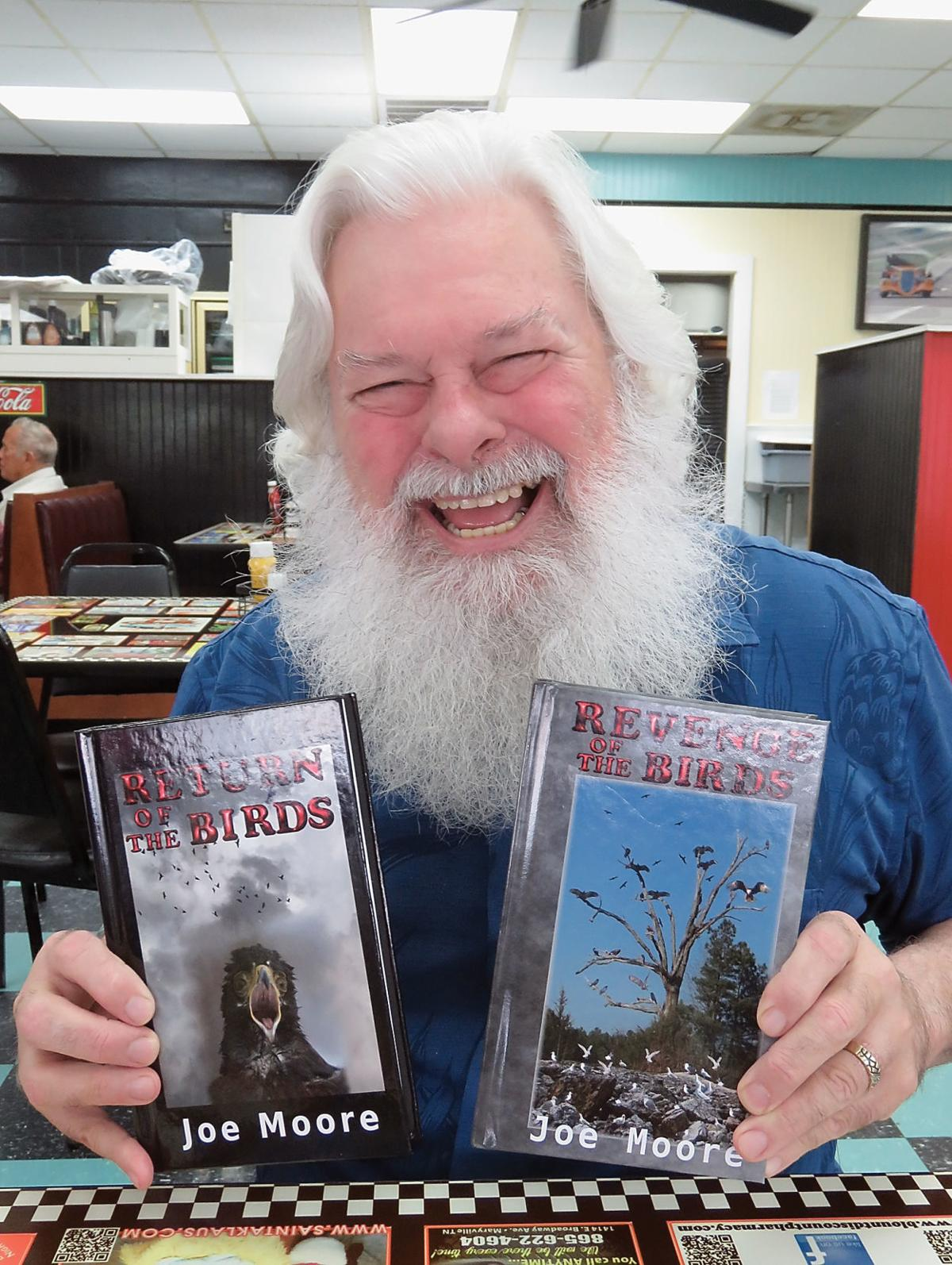 """Author Joe Moore holds copies of his books, """"Return of the Birds"""""""
