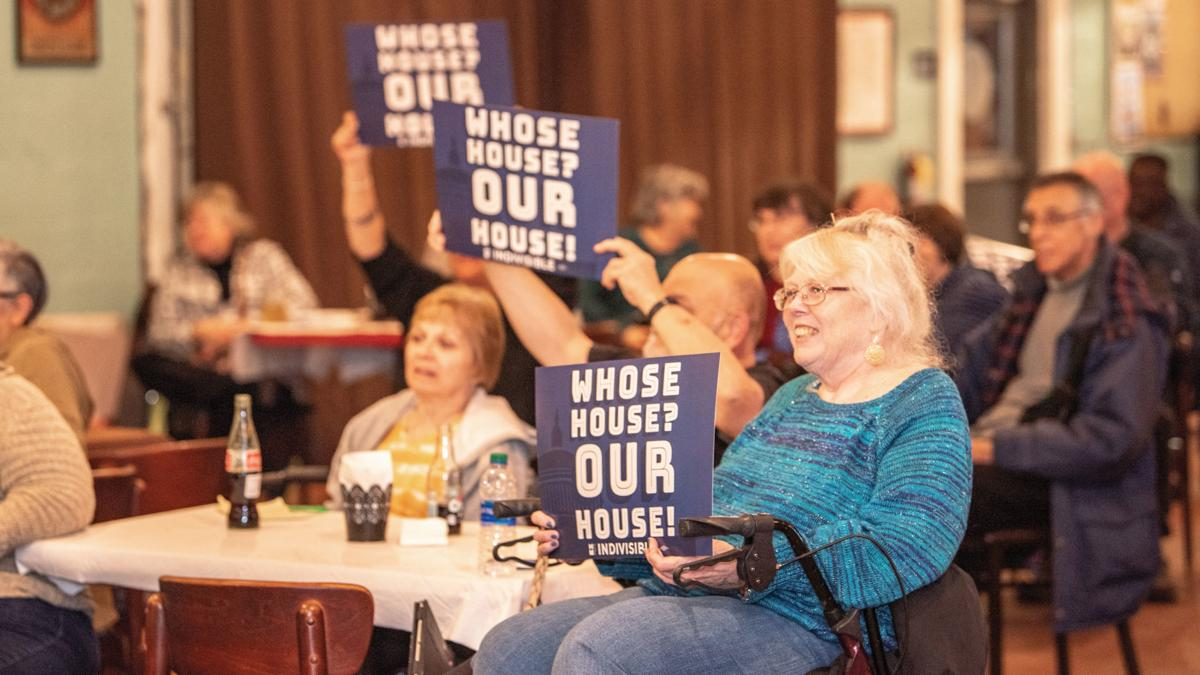 Audience members hold up signs at an Indivisible Project meeting