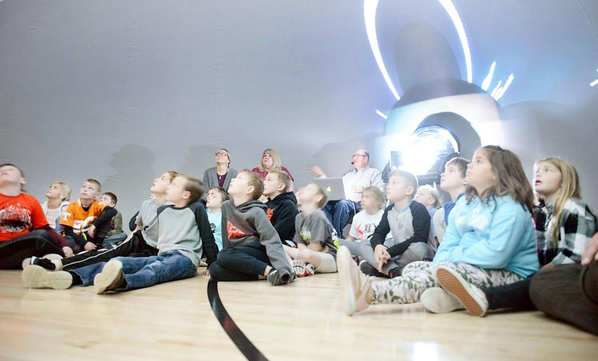 Greenback School third graders listen to a story about the constellations inside a portable planetarium