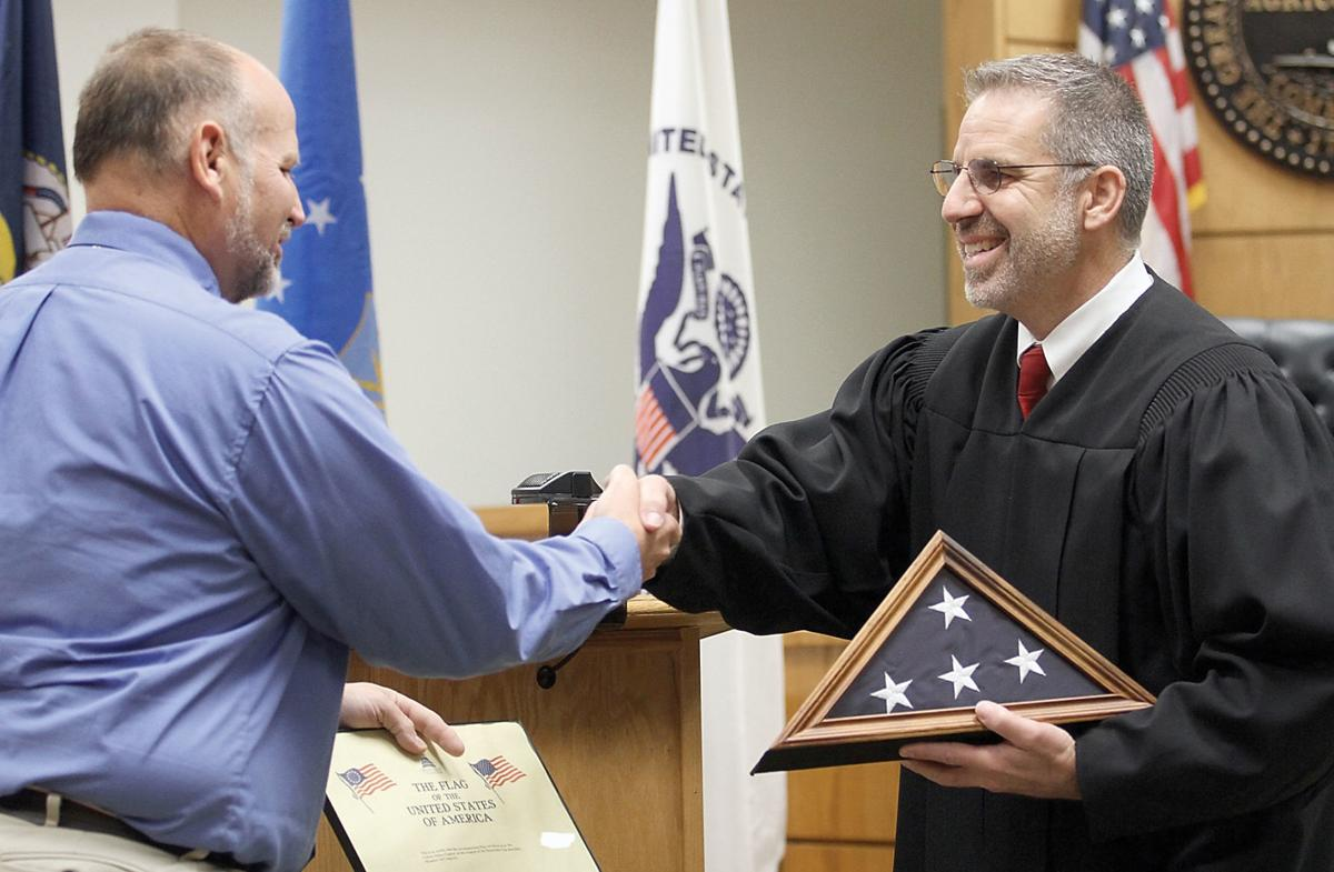 Charles Quiett receives an American flag from Judge Michael Gallegos