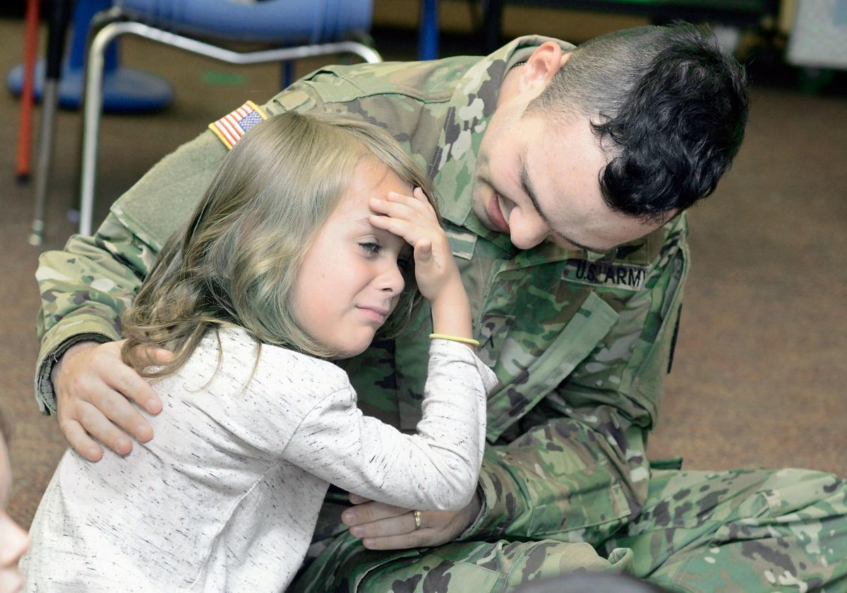 Father son hug during surprise homecoming at Alcoa Elementary School