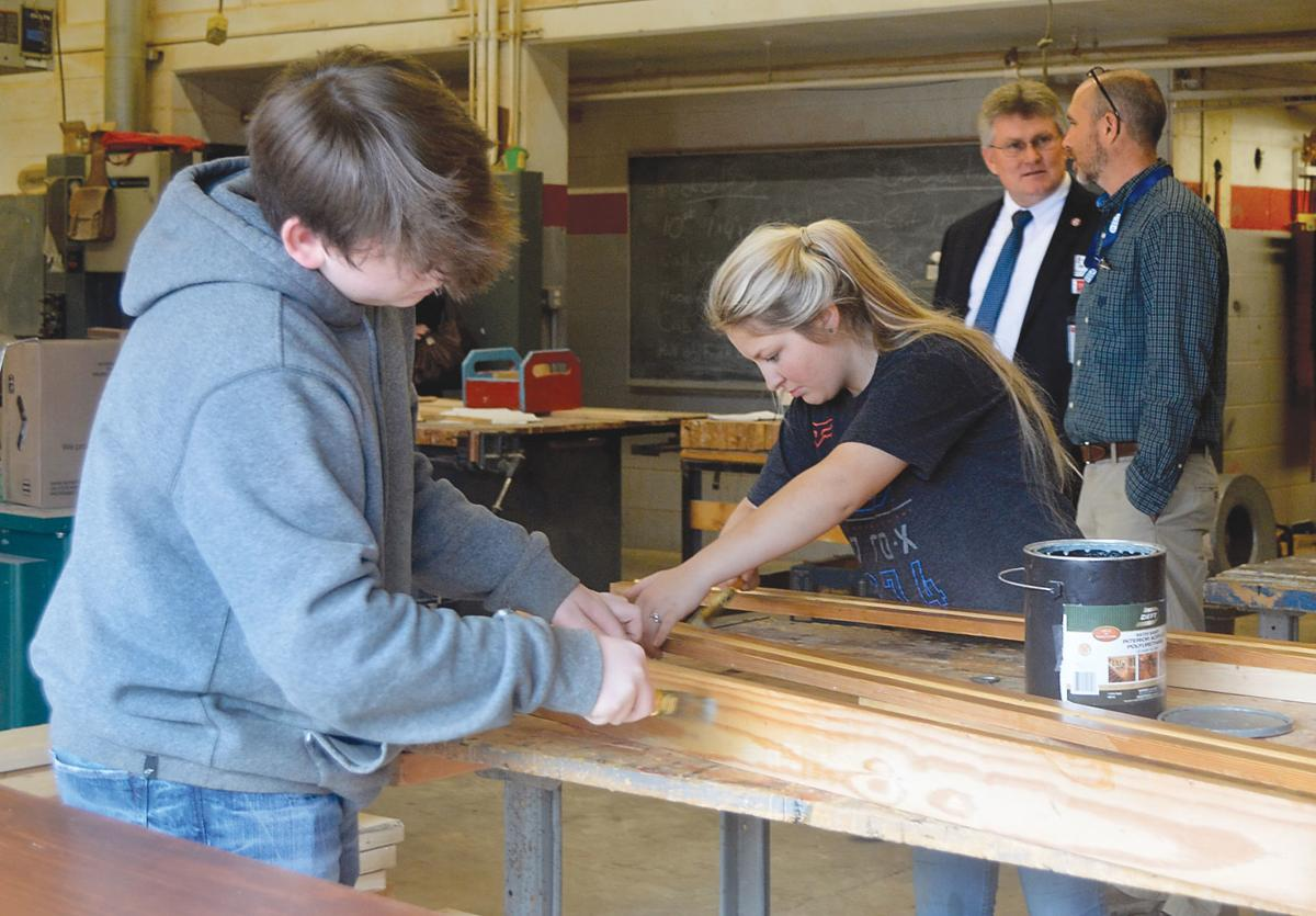 Lylie Ailshie, deputy education commisioner, talks with Heritage High School teacher Jason Tipton while students finish wood