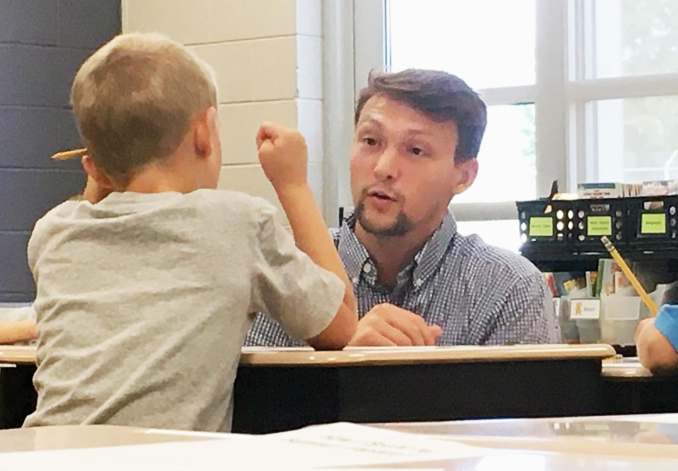 Teacher Addison Hatfield talks with second grader at Carpenters Elementary School