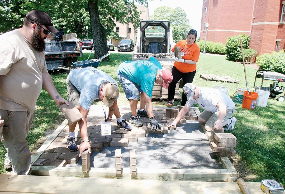 Kin Takahashi Week volunteers lay bricks for a picnic table pad outside Lloyd Hall at Maryville College