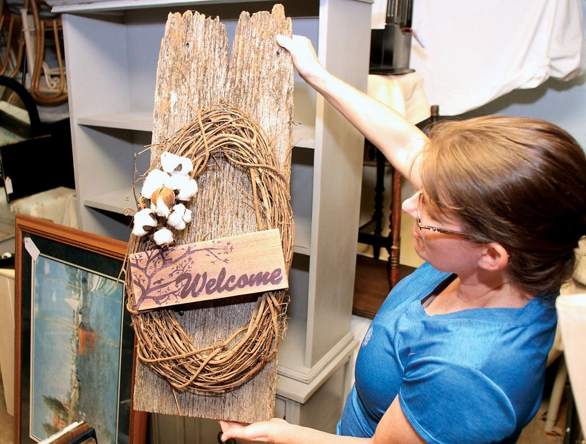 Carol Lucas shows a welcome sign made from barn wood