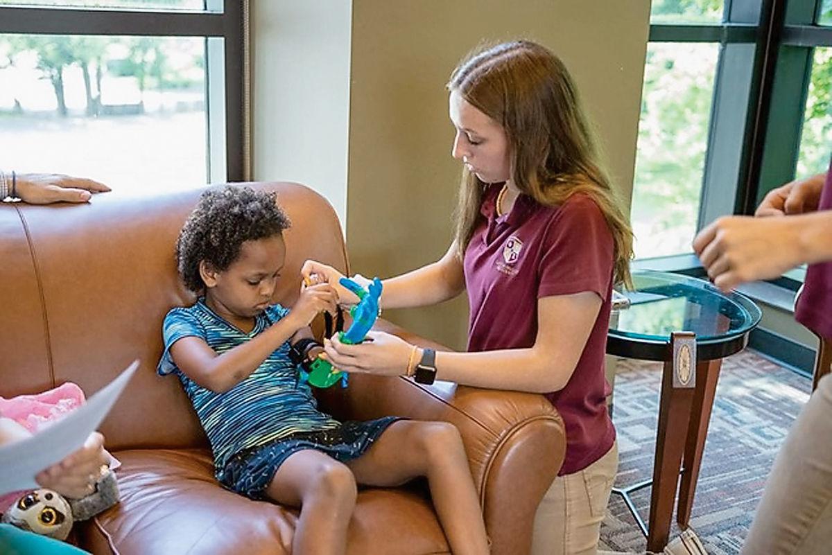 Clayton-Bradley Academy student Caroline Stedina straps a prosthetic arm on 6-year-old Aniyah Irwin of Tunisia
