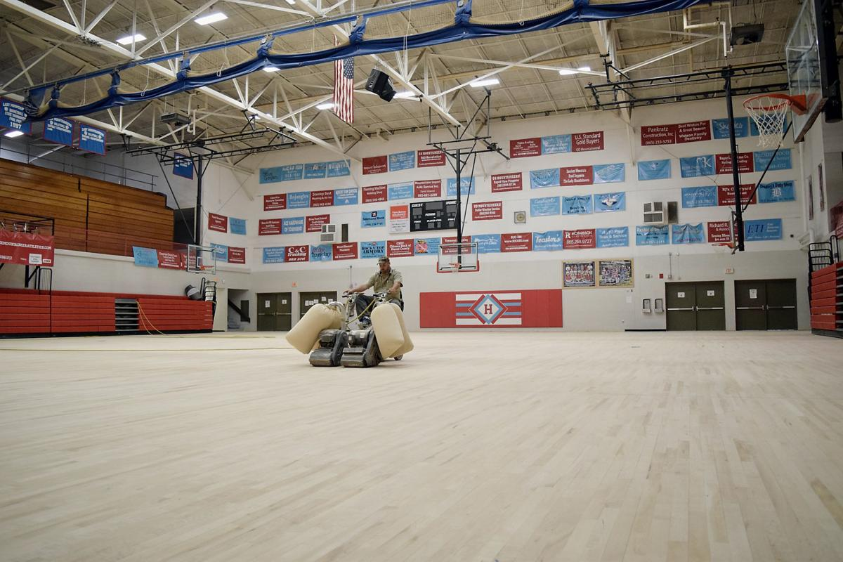 Finchum works on Heritage High School gym floor