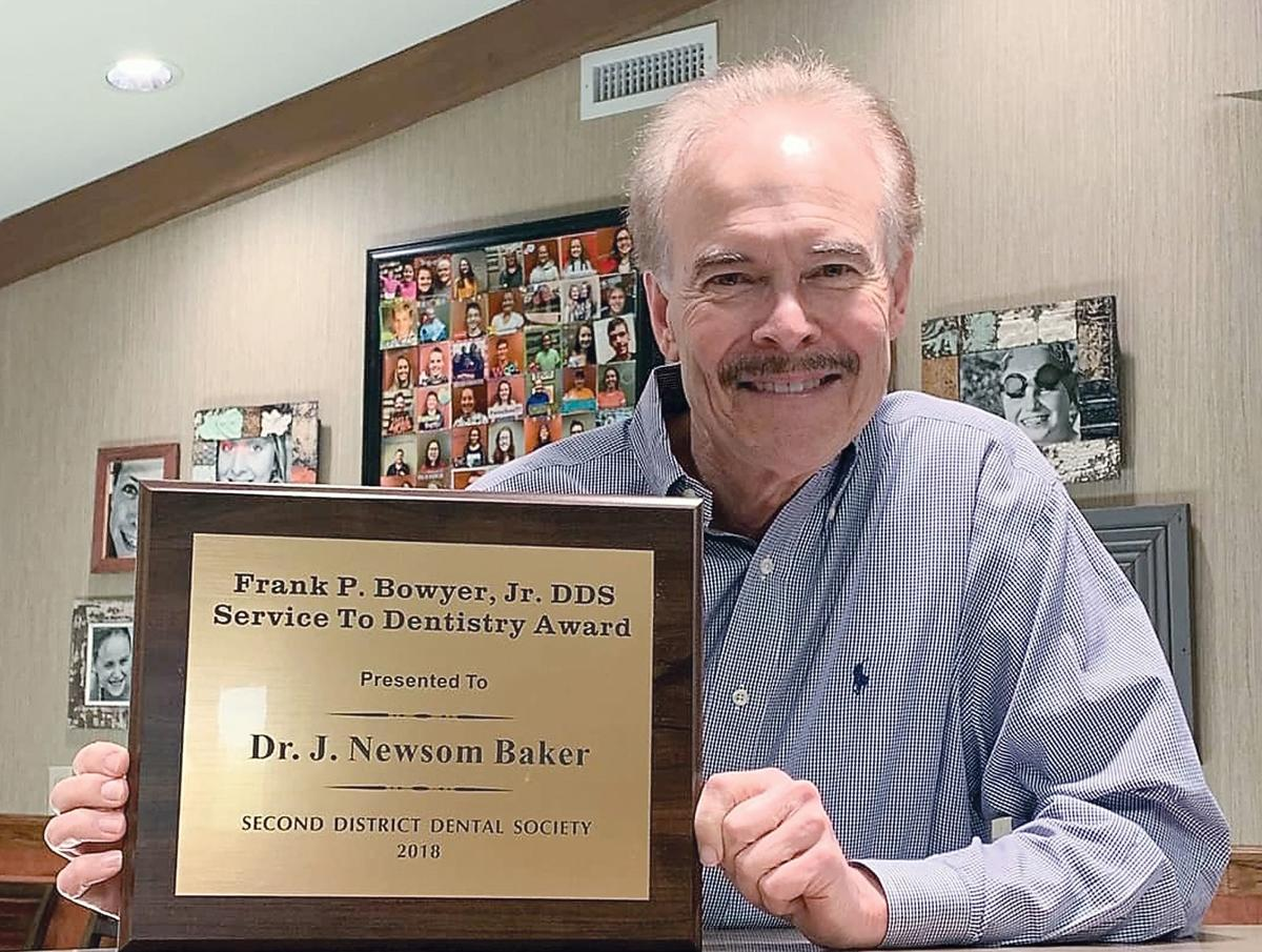J. Newsom Baker, DDS, MS in orthodontics, holds a plaque recognizing his service in dentistry