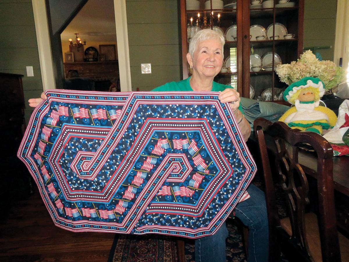 Barbara Davis holds a patriotic table runner she made