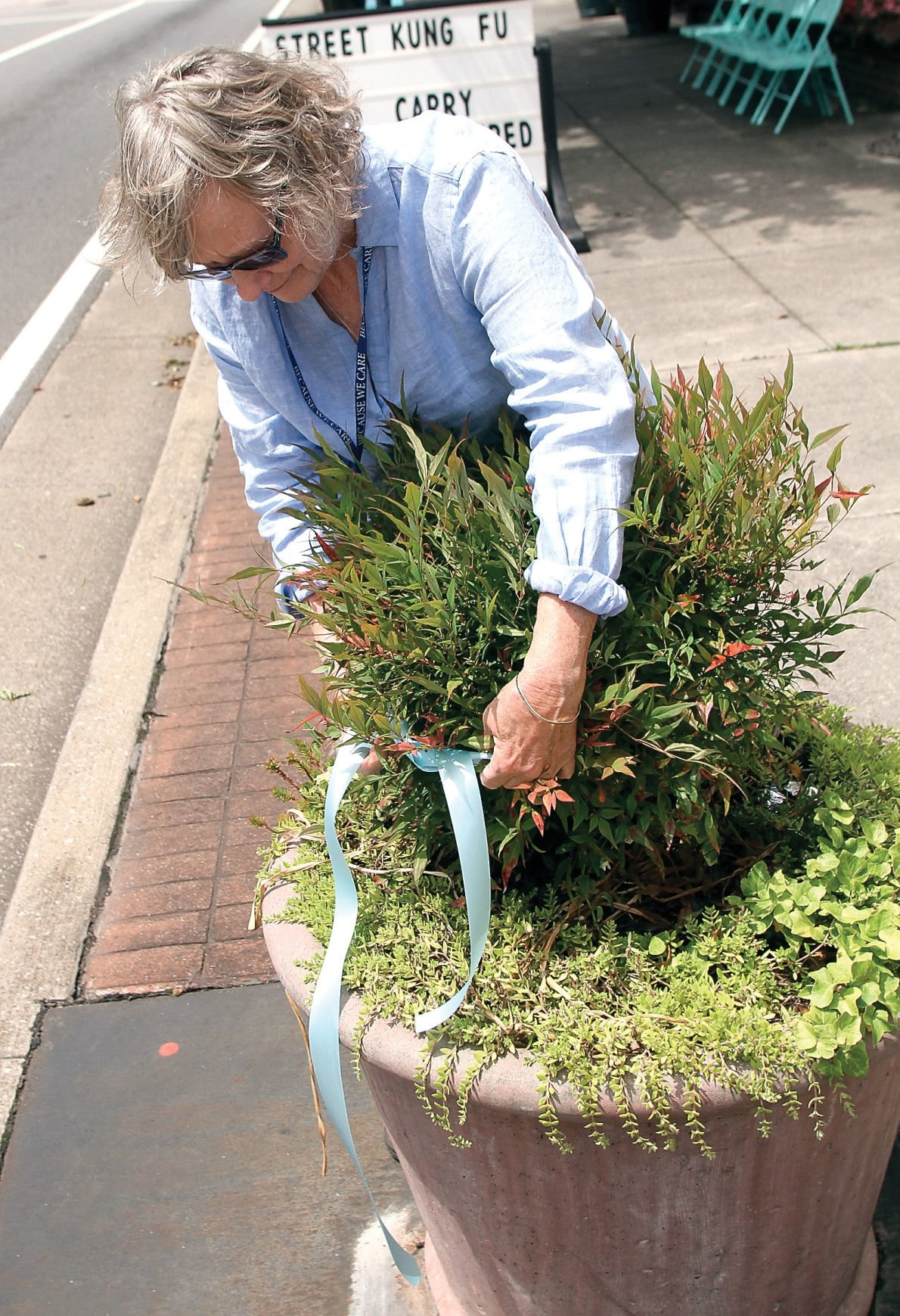 Shelly Robinson ties a blue ribbon around plant along Broadway