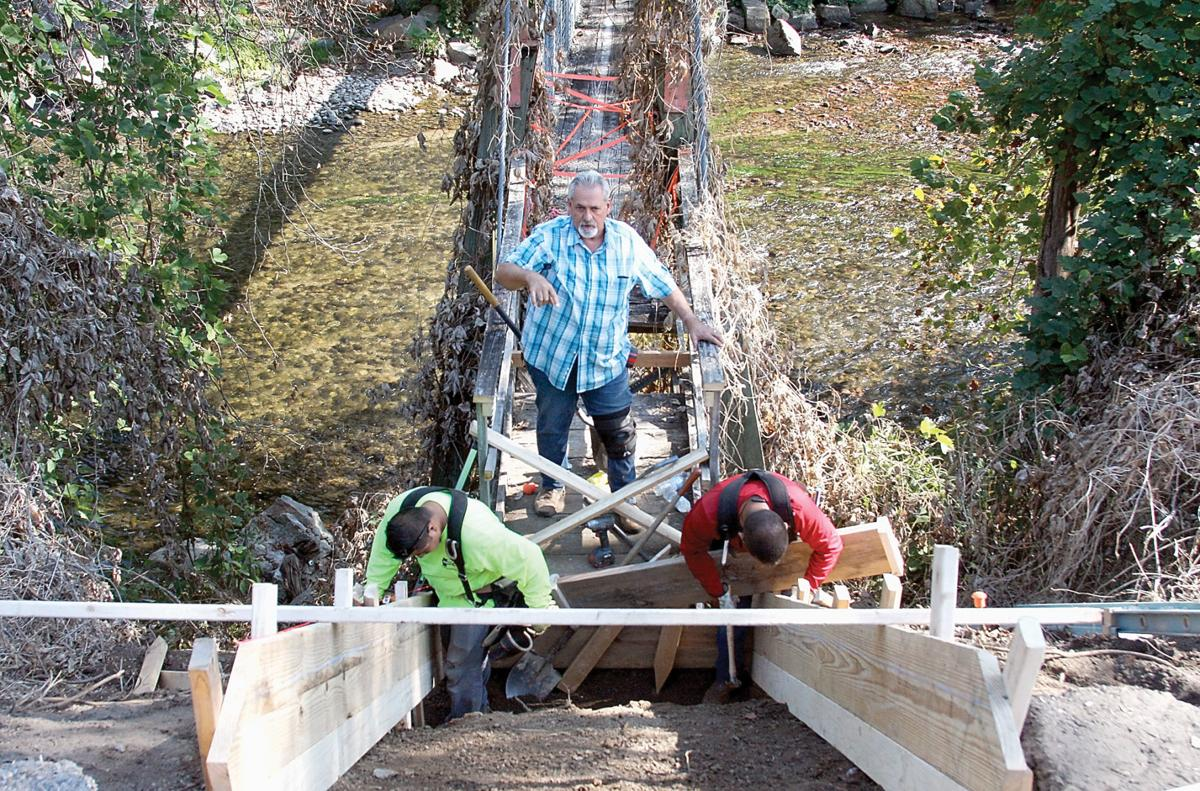 Workers start repairs on the swinging bridge in Townsend