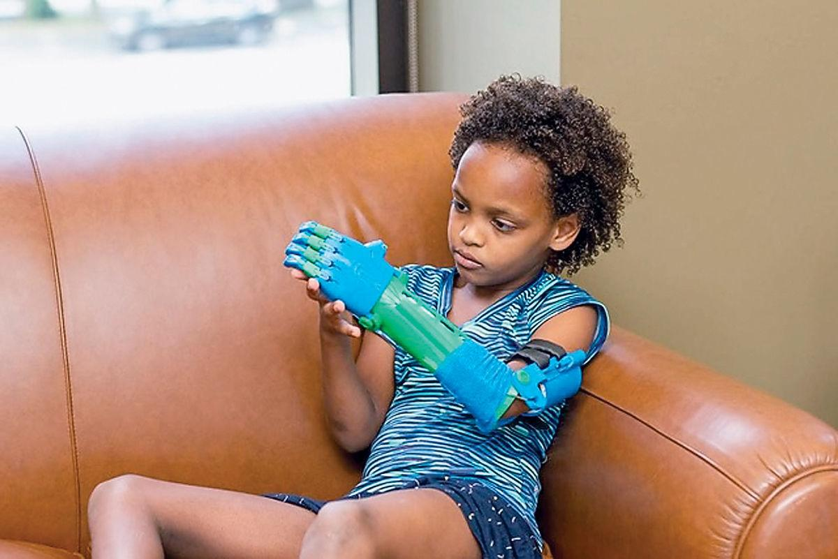 Aniyah Irwin of Tunisia studies prosthetic arm created for her by Clayton-Bradley Academy students